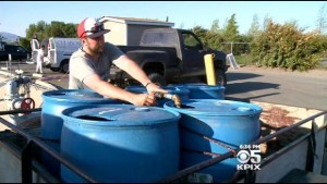 Man fills drums for free recycled water fill station in Dublin. (CBS)