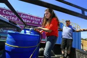 Sonoma County Water Agency intern Aylin Erden helps John Petroni of Sonoma fill two large barrels with treated wastewater from the Sonoma Valley Water Treatment plant to irrigate the redwood trees on his property. (JOHN BURGESS / The Press Democrat)